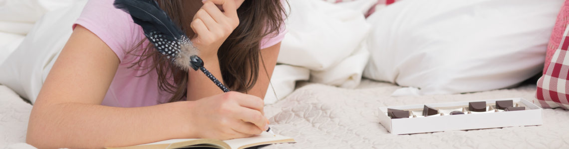 Young woman lying in bed and writing diary