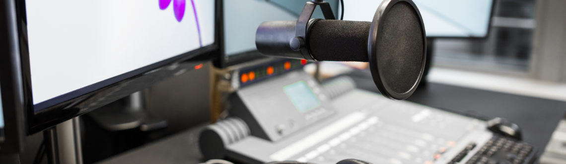 Closeup of microphone with music mixers and headphones by monitors on table in radio studio